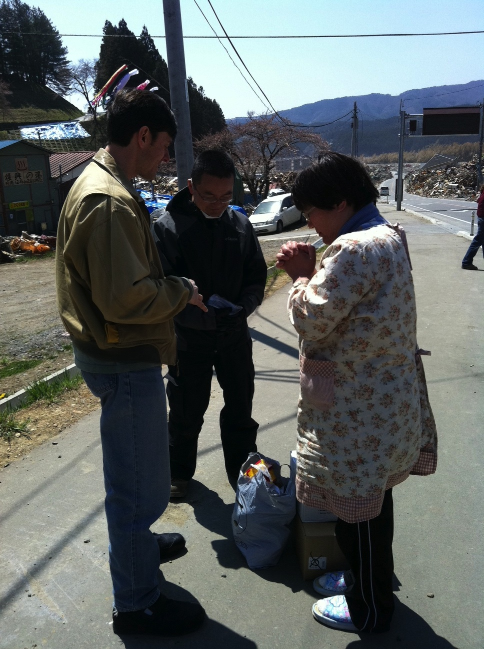 Kent Muhling prays with people following the tsunami in Japan