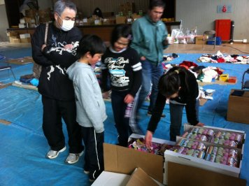 Picking through supplies at a relief center.